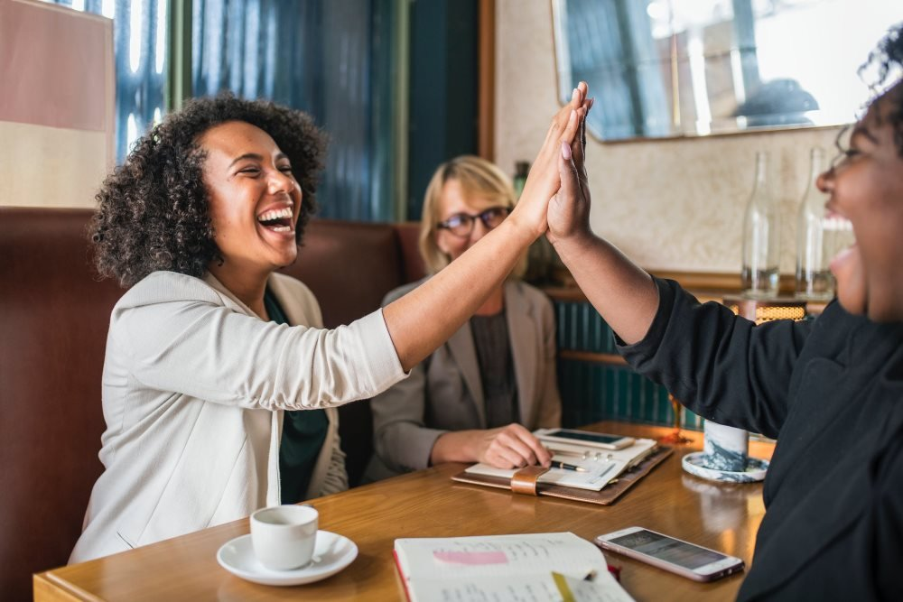 Frauen schlagen Hände ein und Lachen